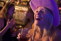 Junge Frau im Cowboyhut lachend an einem Nachtklub Stockbild
