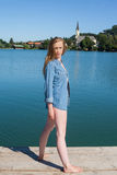 Junge Frau im Denim-Hemd, das auf See-Dock steht Lizenzfreies Stockfoto