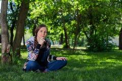 Junge Frau im Denimoverall, der auf dem grünen Gras im Park sitzt stockfotografie
