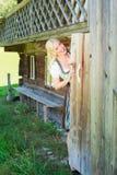 Junge Frau im Dirndl schaut aus der Toilettentür heraus Lizenzfreies Stockfoto