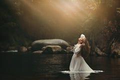 Junge Frau im feenhaften Teich stockfoto