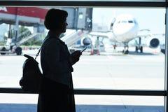Junge Frau im Flughafen, betrachtend durch das Fenster Flugzeugen lizenzfreies stockfoto