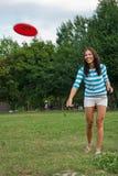 Junge Frau im Freien, einen Frisbee werfend Lizenzfreie Stockfotos