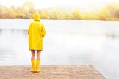 Junge Frau im gelben Regenmantel und in den Gummistiefeln Stockfotos