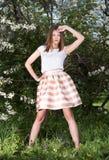 Junge Frau im gestreiften Rock, der in einem blühenden Frühlingsgarten aufwirft Lizenzfreie Stockfotos