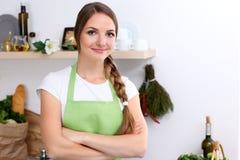Junge Frau im grünen Schutzblech strebt das Kochen in einer Küche an Hausfrau schmeckt die Suppe durch hölzernen Löffel Stockbild
