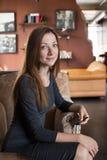 Junge Frau im grauen Kleid, das im Café sitzt Lizenzfreie Stockbilder