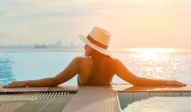 Junge Frau im Großen Hut, der auf der Schwimmen sich entspannt Lizenzfreie Stockfotos