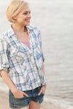 Junge Frau im Hemd und in Jeans, die auf Seeufer stehen Lizenzfreies Stockfoto