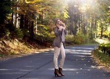 Junge Frau im Herbst, der auf Straße bleibt Lizenzfreie Stockfotos