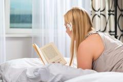 Junge Frau im Hotellesebuch im Bett Lizenzfreie Stockbilder