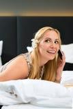 Junge Frau im Hotellesebuch im Bett Lizenzfreies Stockbild