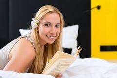Junge Frau im Hotellesebuch im Bett Stockbild