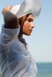 Junge Frau im Hut, der draußen durch das Meer stillsteht Lizenzfreies Stockbild