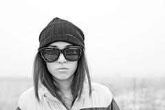 Junge Frau im Hut und in den Sonnenbrillen im Winter Stockfoto