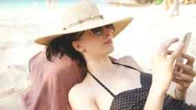 Junge Frau im Hut und in der Sonnenbrille unter Verwendung des Smartphone und in den Lügen auf Strand Lizenzfreie Stockfotos
