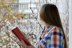 Junge Frau im karierten Hemd mit einem Buch in den Händen steht das Fenster, Frühlingsstadt bereit Stockfotos