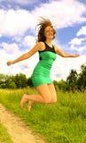 Junge Frau im Kleid, das oben springt Stockfoto