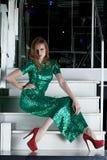 Junge Frau im Kleid des langen Grüns, das auf Treppen sitzt Stockbild