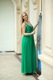 Junge Frau im Kleid des langen Grüns unter Verwendung eines automatisierter Erzähler machin Stockfotografie