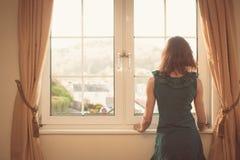 Junge Frau im Kleid, welches heraus das Fenster schaut Stockfoto