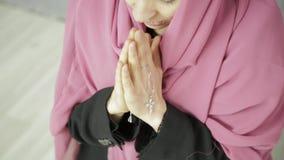Junge Frau im Kopftuch betet weibliche Hände der Nahaufnahme halten Ketten mit einem Kreuz stock video footage