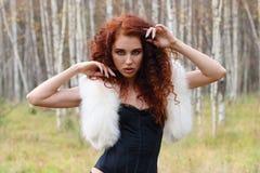 Junge Frau im Korsett mit Pelz und dem gelockten Haar lizenzfreie stockfotografie