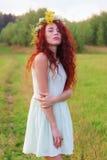 Junge Frau im Kranz und im Kurzschlusskleid wirft auf Wiese an auf Lizenzfreies Stockfoto