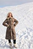 Junge Frau im langen Mantel, der auf schneebedecktem Bereich steht Stockfoto