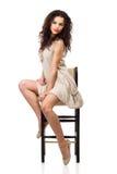 Junge Frau im Leinenkleid, das auf hohem Stuhl sitzt Lizenzfreie Stockfotografie