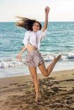 Junge Frau im lustigen Jump-Shot an der Küste Stockfoto
