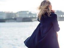 Junge Frau im Mantel draußen stockbilder