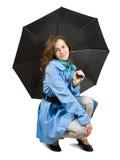 Junge Frau im Mantelholdingregenschirm stockfoto