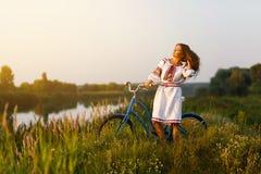 Junge Frau im nationalen ukrainischen Volkskostüm mit Fahrrad Lizenzfreie Stockfotos