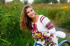 Junge Frau im nationalen ukrainischen Volkskostüm mit Fahrrad Lizenzfreies Stockfoto