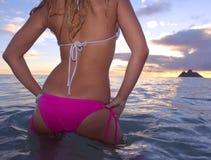 Junge Frau im Ozean am Sonnenaufgang Lizenzfreies Stockfoto