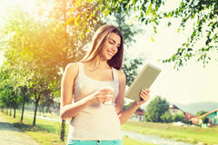 Junge Frau im Park mit Tablette und Mitnehmerkaffee Stockfotos