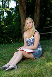 Junge Frau im Parkschreiben im Journal oder im Tagebuch Stockfotografie