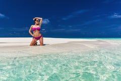 Junge Frau im purpurroten Bikini auf Sanddüne von einer Tropeninsel Stockfoto