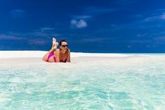 Junge Frau im purpurroten Bikini, der auf Sand auf tropischem Strand sich entspannt lizenzfreie stockfotos