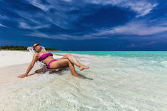 Junge Frau im purpurroten Bikini, der auf Stuhl im tropischen Wasser sich entspannt stockbild