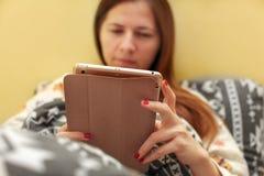 Junge Frau im Pyjama, legend in das Bett, bedeckt mit Daunendecke, workin lizenzfreie stockfotos