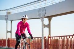 Junge Frau im rosa Jacken-Reitstraßen-Fahrrad auf der Brücken-Fahrrad-Linie in kalten Sunny Autumn Day Gesunder Lebensstil lizenzfreies stockfoto