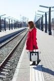 Junge Frau im Rot an einer Bahnstation Stockfotos