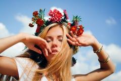 Junge Frau im roten Blumenkranz mit geschlossenen Augen Stockbilder