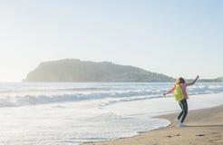 Junge Frau im roten karierten Hemd, in den Jeans, in den weißen Turnschuhen gehend entlang Strand und im stürmischen Ozean am son Lizenzfreie Stockfotografie