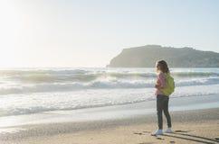 Junge Frau im roten karierten Hemd, in den Jeans, in den weißen Turnschuhen gehend entlang Strand und im stürmischen Ozean am son Stockfoto