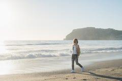 Junge Frau im roten karierten Hemd, in den Jeans, in den weißen Turnschuhen gehend entlang Strand und im stürmischen Ozean am son Stockbilder