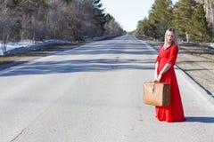 Junge Frau im roten Kleid auf Straße mit rotem Gepäck Stockfoto