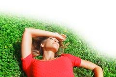 Junge Frau im roten Kleid, das auf Gras liegt Stockfotografie